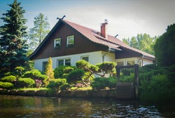 House with a triangular roof on the river bank, surrounded by a garden with green plants and a well. House of traditional architecture in the city Lübbenau,  Spreewald, Germany.