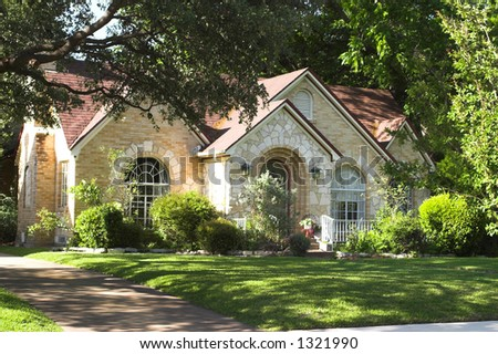 house with beautiful mixture of light colored and white stone and brick; arched windows and entryway; surrounded by green foliage