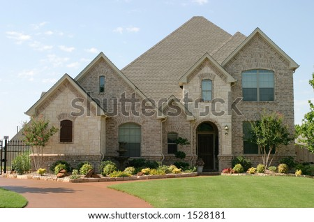 house with beautiful mixture of light colored and white stone and brick; arched windows and entryway.