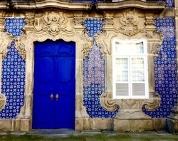 House with blue doors and blue ceramics. Building facade with azulejo. Braga, Portugal.
