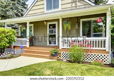 House with cozy entrance porch. White railings blend with brown wooden floor and green house exterior