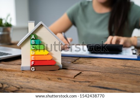 House With Energy Efficiency Rate In Front Of Businessperson Working In Office While Using Calculator Сток-фото ©