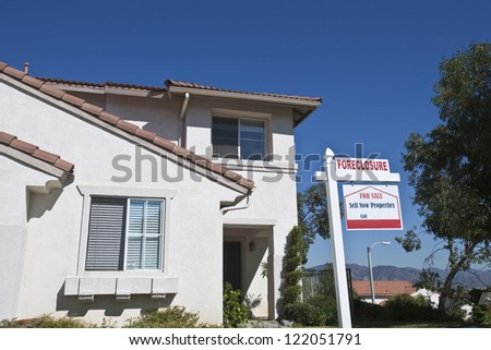 House with foreclosure sign against blue sky