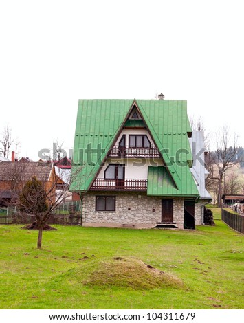 House with green roof and stone cladding