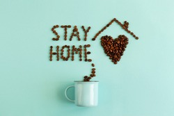 House with heart and stay home sign from coffee beans on light blue background. Staying at home with self quarantine. Right morning - stay home and drink coffee. Actual flat lay with coffee cup