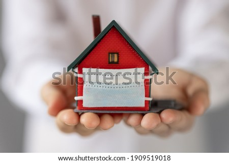 House with medical mask in children`s hands. Coronavirus COVID-19 pandemic. Stay home concept Foto stock ©