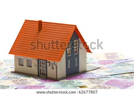 House with money over white background - mortgaging concept
