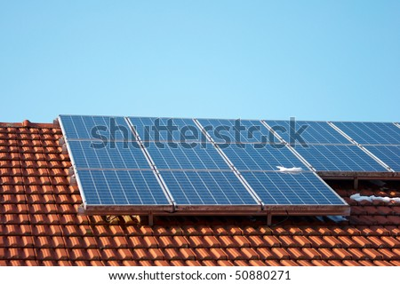 house with solar panels and blue sky in the background