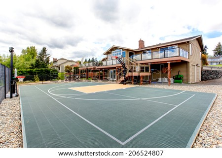 House with sport court and patio area. View of green court