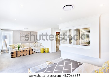 House with white ceiling and wall in the living room including a wooden box and fancy flowering plant beside the sofa and pillows, the stand lamp near to the window, there is a bed and a washroom
