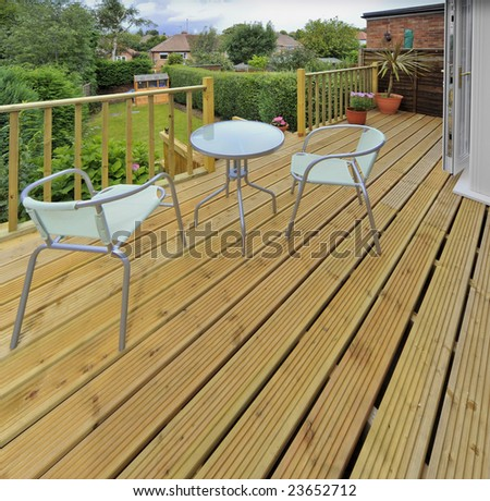 house with wooden decking and patio leading to garden