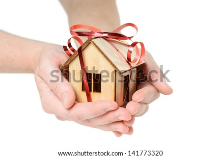 House Wooden in both hands with red ribbon - isolated on white background