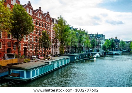 Houseboat barge at daytime along the riverside, Amsterdam canal - Holland Netherlands