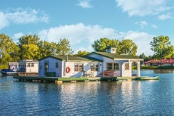 Houseboats on pond in Lake Erie built on pontoons on barrels with rowboats tied up to porch.