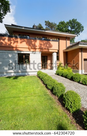 Housefront of a travertine house with the regular bushes surrounding the pathway directing to front door #642304720