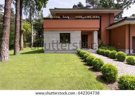 Housefront of a travertine house with the regular bushes surrounding the pathway directing to front door #642304738
