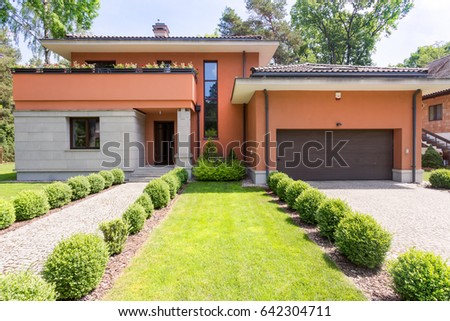 Housefront of a travertine house with the regular bushes surrounding the pathways directing to front door and the garage #642304711