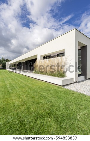 Housefront of modern villa surrounded by grass #594853859