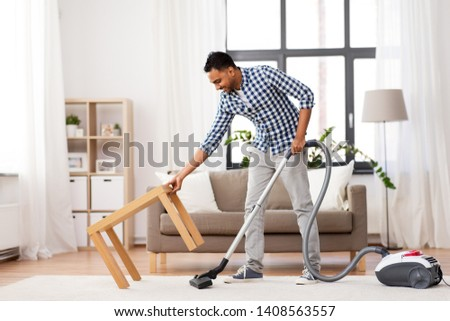 household and cleaning concept - indian man with vacuum cleaner at home #1408563557