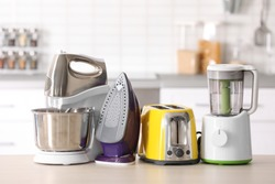 Household and kitchen appliances on table against blurred background