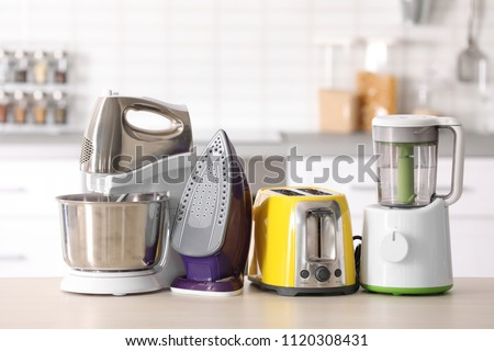 Household and kitchen appliances on table against blurred background #1120308431