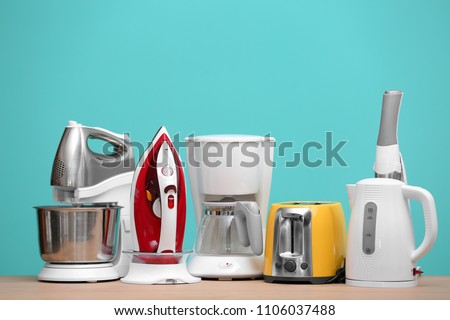 Household and kitchen appliances on table against color background. Interior element #1106037488