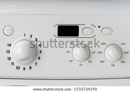 Household appliances concept. A part of washing machine control panel. Program selection, temperature and spin knobs.