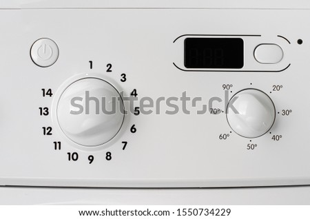 Household appliances concept. A part of washing machine control panel. Program selection and temperature knobs.