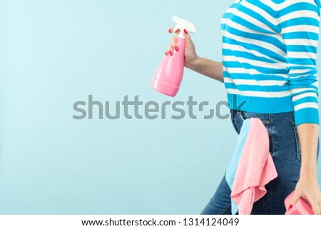 Household chores. Organized housewife. Woman holding atomizer and sponge with cloth in pocket. Copy space on blue background. #1314124049