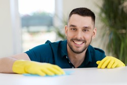 household, cleaning and people concept - smiling man wiping table with cloth at home