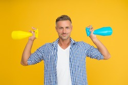 Household cleaning products kill coronavirus. Happy guy hold spray bottles. Using household cleaners and disinfectants. Household hygiene. Routine cleaning and disinfection of household.