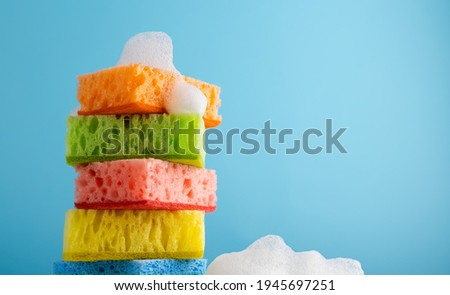 Household Cleaning Scrub Colored Sponges with soap foam. Kitchen Dishwashing Sponge on blue background. Cleaning home concept. Space for text. Foto stock ©