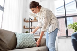 household, home improvement and cleaning concept - happy smiling woman arranging cushions on armchair and sofa