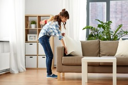 household, housework and cleaning concept - asian woman arranging sofa cushions at home
