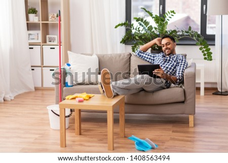 household, housework and technology concept - indian man with tablet computer, mop and bucket after home cleaning #1408563494