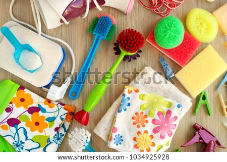 Household items are gathered together. View from above. Brushes, rubber gloves, washing powder, foam sponge, clothespins are household items. Household items for hygiene and cleanliness. #1034925928