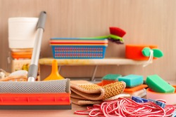 Household items. Household goods are collected in a heap. An ironing board, a clothesline, clothespins, toilet paper, plastic boxes, a brush for glasses, sponges for utensils are household utensils.