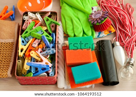 Household items. Household items in the form of rubber gloves, light bulbs, sponges, garbage bags, dishcloths, clothespins. Home stuff. Various household items in a pile. #1064193512