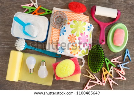 Household items of various kinds. View from above. Washing powder, garbage bags, LED lamp, clothes roller, soap and clothespins are household utensils. Household items for cleanliness in the house. #1100485649