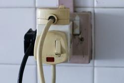 Household multi socket plug overloaded with old plugs. UK 3 pin plug, old with paint peeling