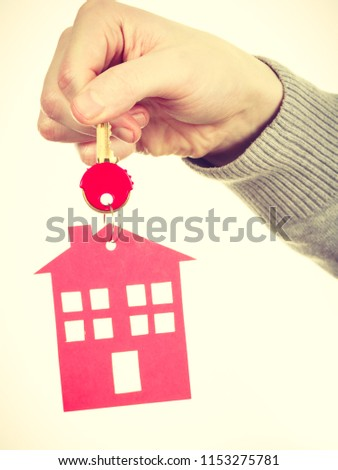 Household ownership security real estate symbolism concept. Key ring with house pendant. Home symbol held by human hand. #1153275781