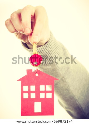 Household ownership security real estate symbolism concept. Key ring with house pendant. Home symbol held by human hand. #569872174