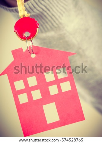 Household ownership security real estate symbolism concept. Key ring with house pendant. Home symbol held by human hand. #574528765