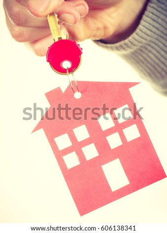 Household ownership security real estate symbolism concept. Key ring with house pendant. Home symbol held by human hand. #606138341