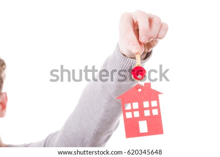 Household ownership security real estate symbolism concept. Key ring with house pendant. Home symbol held by human hand. #620345648