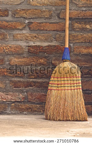 Household Used Broom For Floor Dust Cleaning Leaning on Brick Wall, Vertical