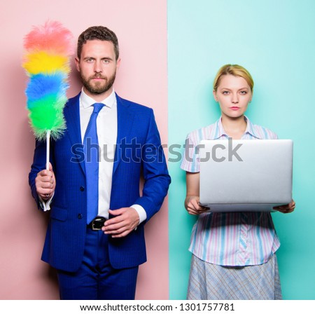 Househusband and female boss. Businessman and housewife. Family couple. Husband stand with dust brush while wife holding laptop. Couple of handsome man and pretty woman. Housekeeping or business. #1301757781