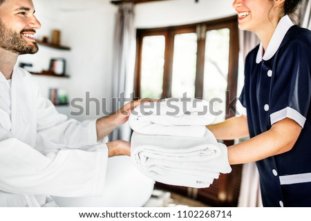 Housekeeper handing over fresh towels #1102268714