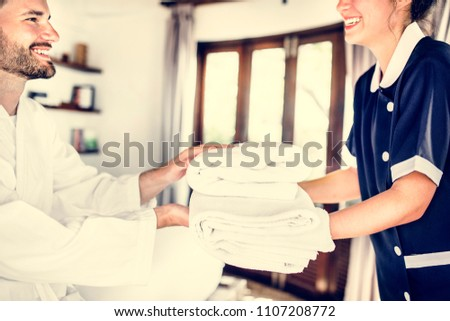 Housekeeper handing over fresh towels #1107208772
