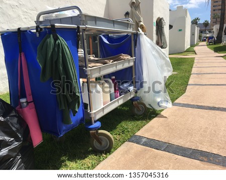 Housekeeper's trolley showing cleaning bottles, bags outside on grass next to path & white buildings with blue sky. Housekeeping for holiday apartments chalets. Taken Tenerife. Landscape orientation #1357045316